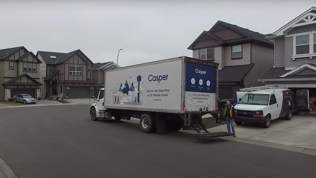 An image of a truck side ad for the company Casper in a neighborhood.
