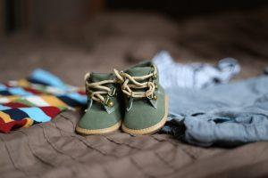 A pair of green baby shoes, some clothes in the background