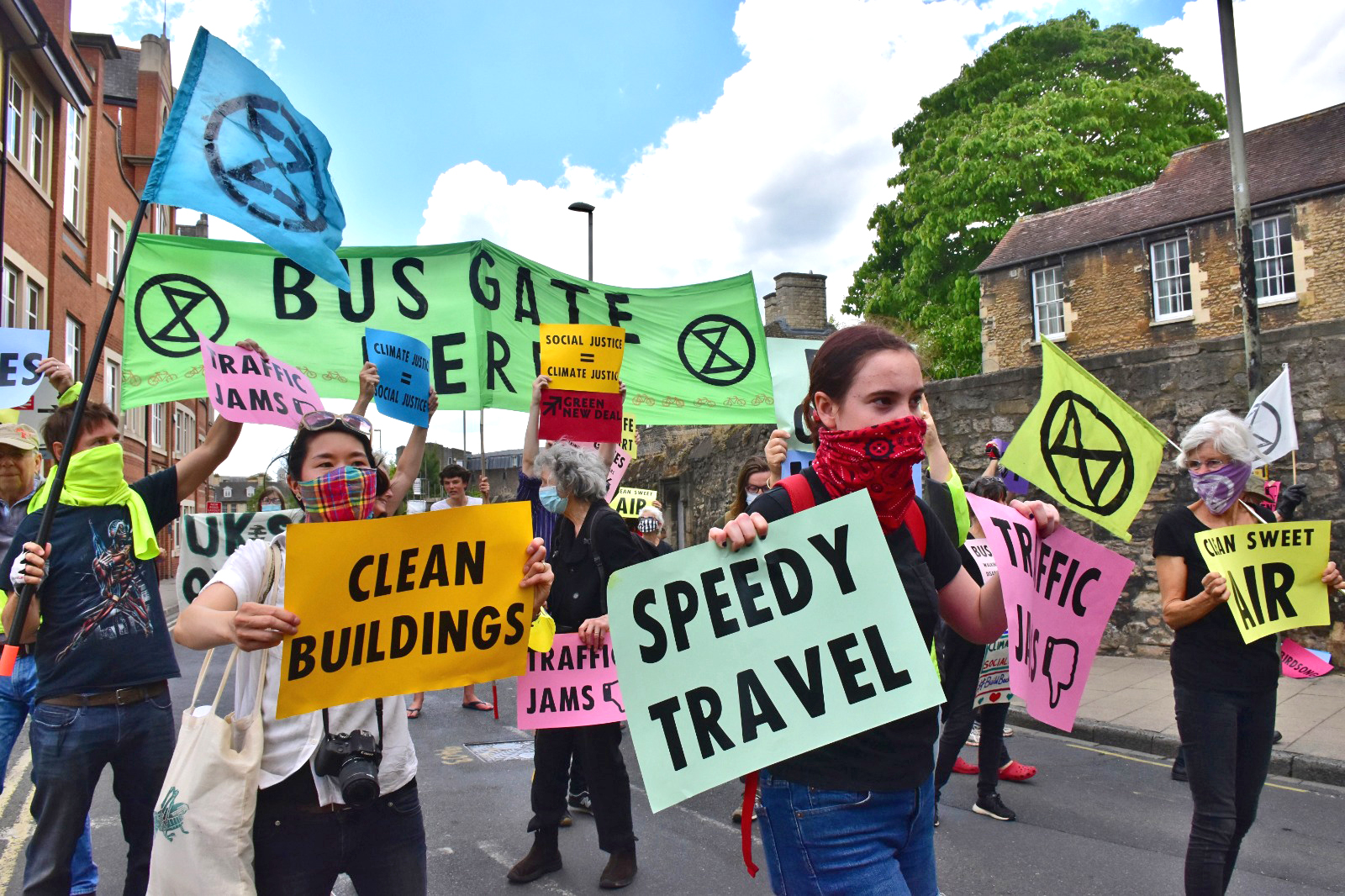 "Rebels blocking Worcester St, Oxford, with signs including ""Clean Buildings"", ""Speedy travel"", ""Clean Sweet Air"", and a banner with the Extinction Symbol and ""Bus Gate Here""."