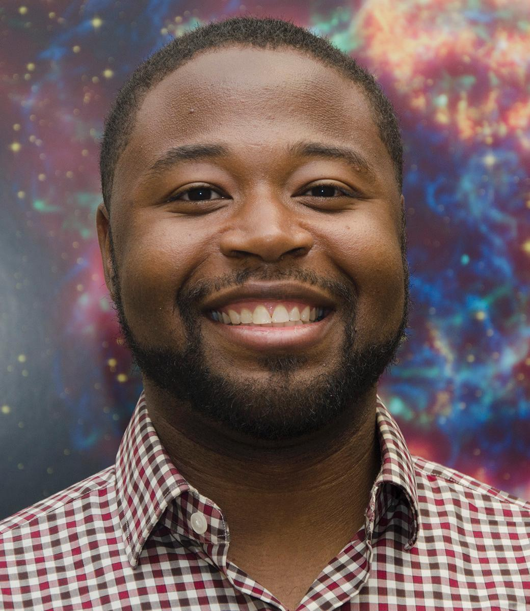 A smiling Black man with short hair and a gingham shirt, with an outer space-y background.