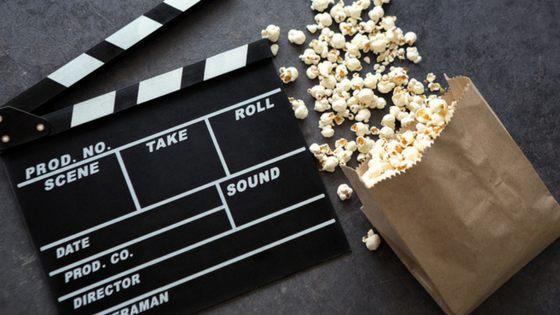 movie clapperboard and bag of popcorn