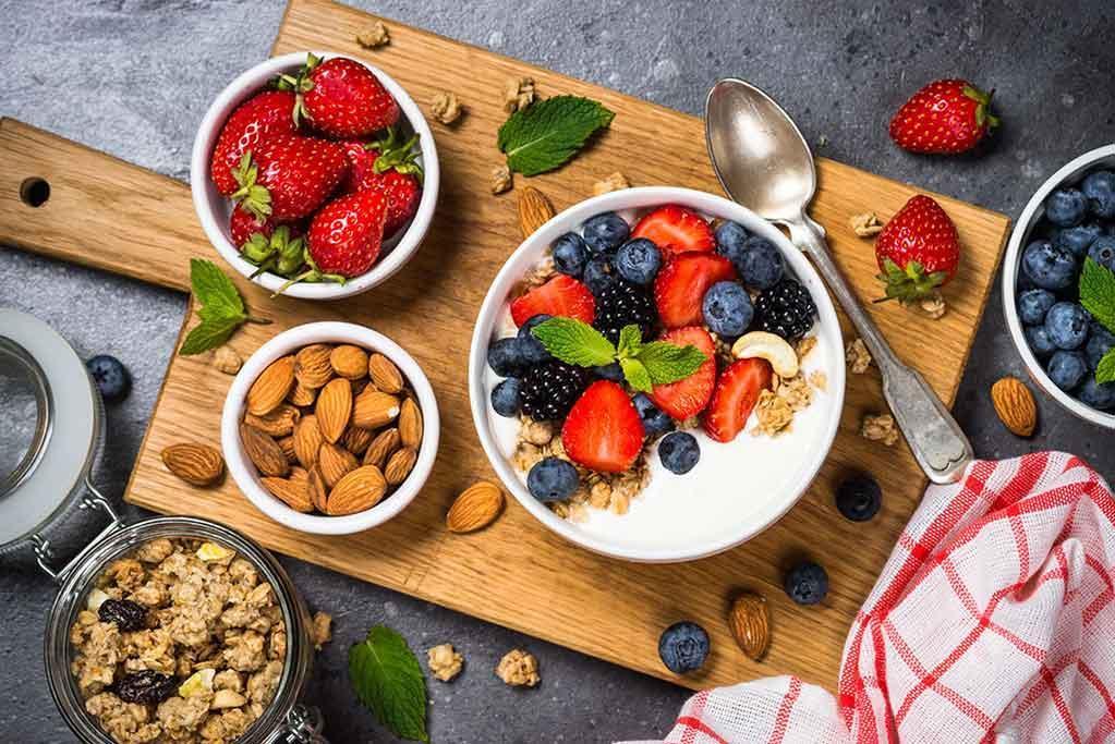 Granola de yaourt grec avec baies fraîches sur table en pierre, vue de dessus. Nourriture saine, en-cas ou petit-déjeuner.