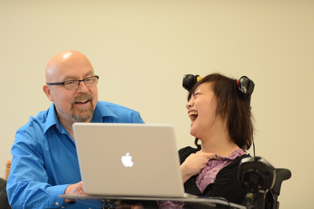 image of Mark Coppin and Sady Paulson laughing as they look at a laptop