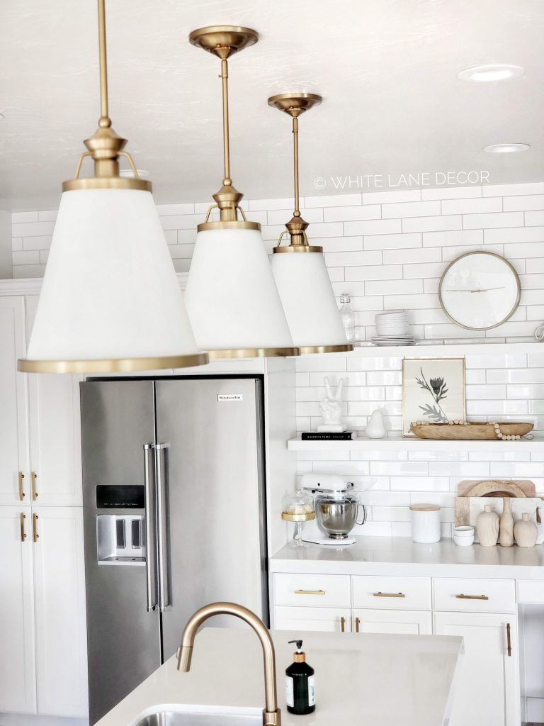 bright white and gold kitchen with white and gold pendant lights, white countertops, white counter to ceiling subway tile backsplash and gold cabinet hardware