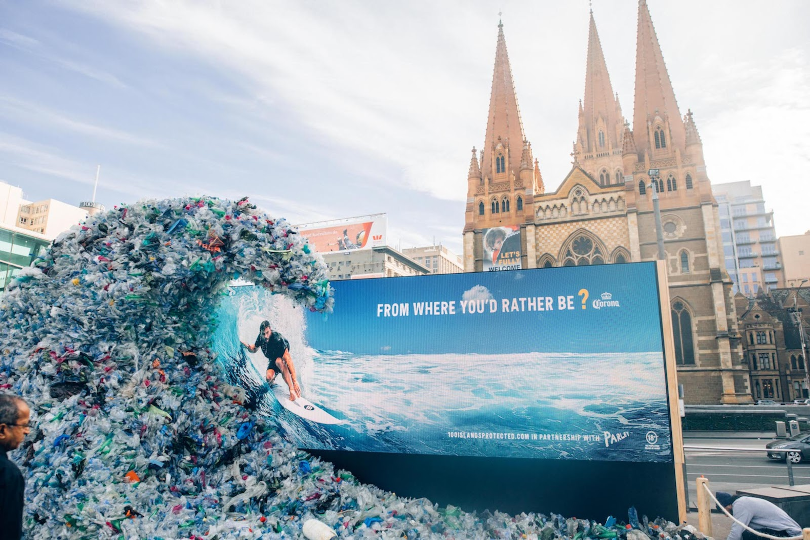 """Giant plastic wave with a billboard behind, showing a man surfing in the real ocean and the text """"From where you'd rather be?"""""""