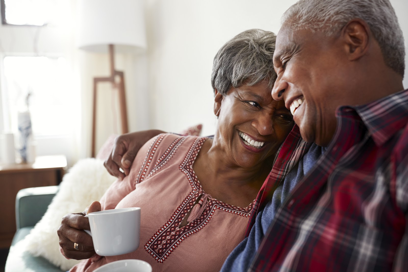 old man and woman smiling while holding a cup