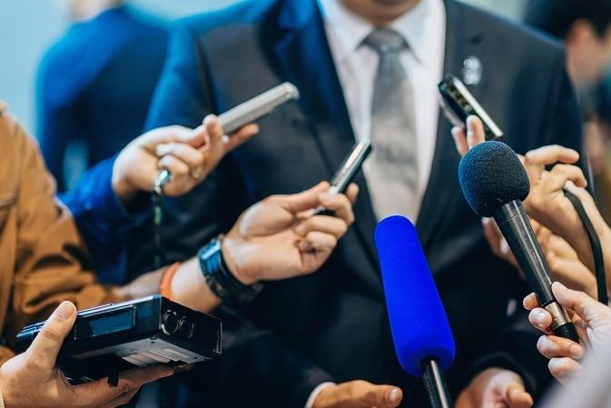 Diversos microfones e gravadores são apontados para um homem, simulando uma entrevista