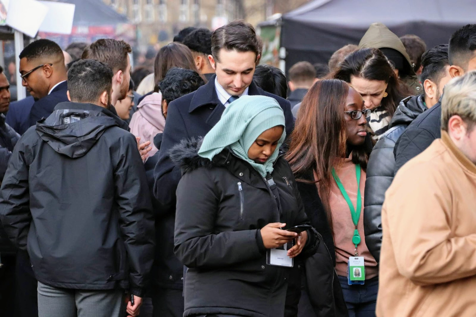 A crowd at a pop up food market wiaiting for their lunch. They are all looking down at their mobile phones