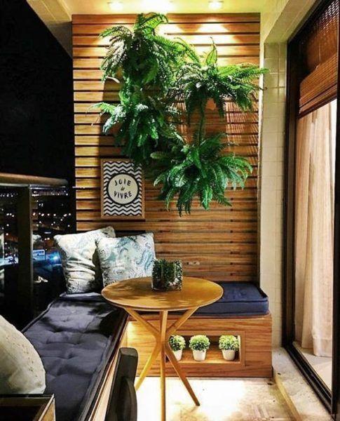 Varanda com painel de madeira com plantas penduradas, móvel planejado de madeira com estofado azul, almofadas e mesinha de centro redonda.