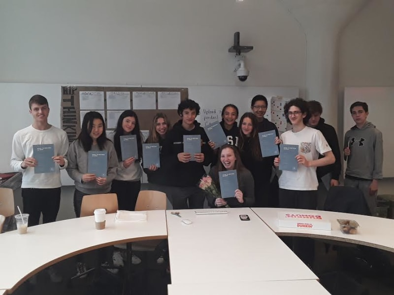 With Olivia sitting at center, students pose with their copies of the published law review