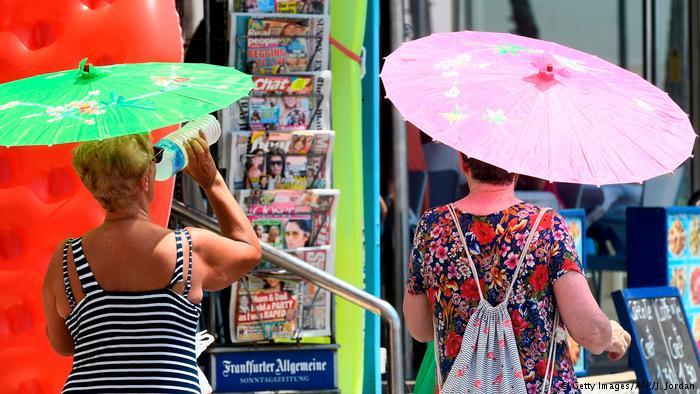 Жара в городе, две женщины под зонтиками