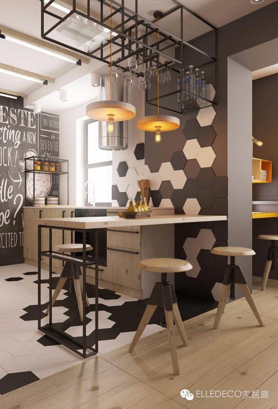 Cozinha em estilo industrial com bancadas, armários e bancos amadeirados, armários de ferro de teto, parede lousa na lateral, piso hexagonal em degrade preto e branco e parede de fundo com azulejo hexagonal preto e branco em degrade.