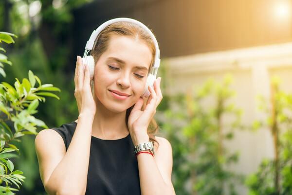 foto de uma mulher loira ouvindo música com um fone de ouvido