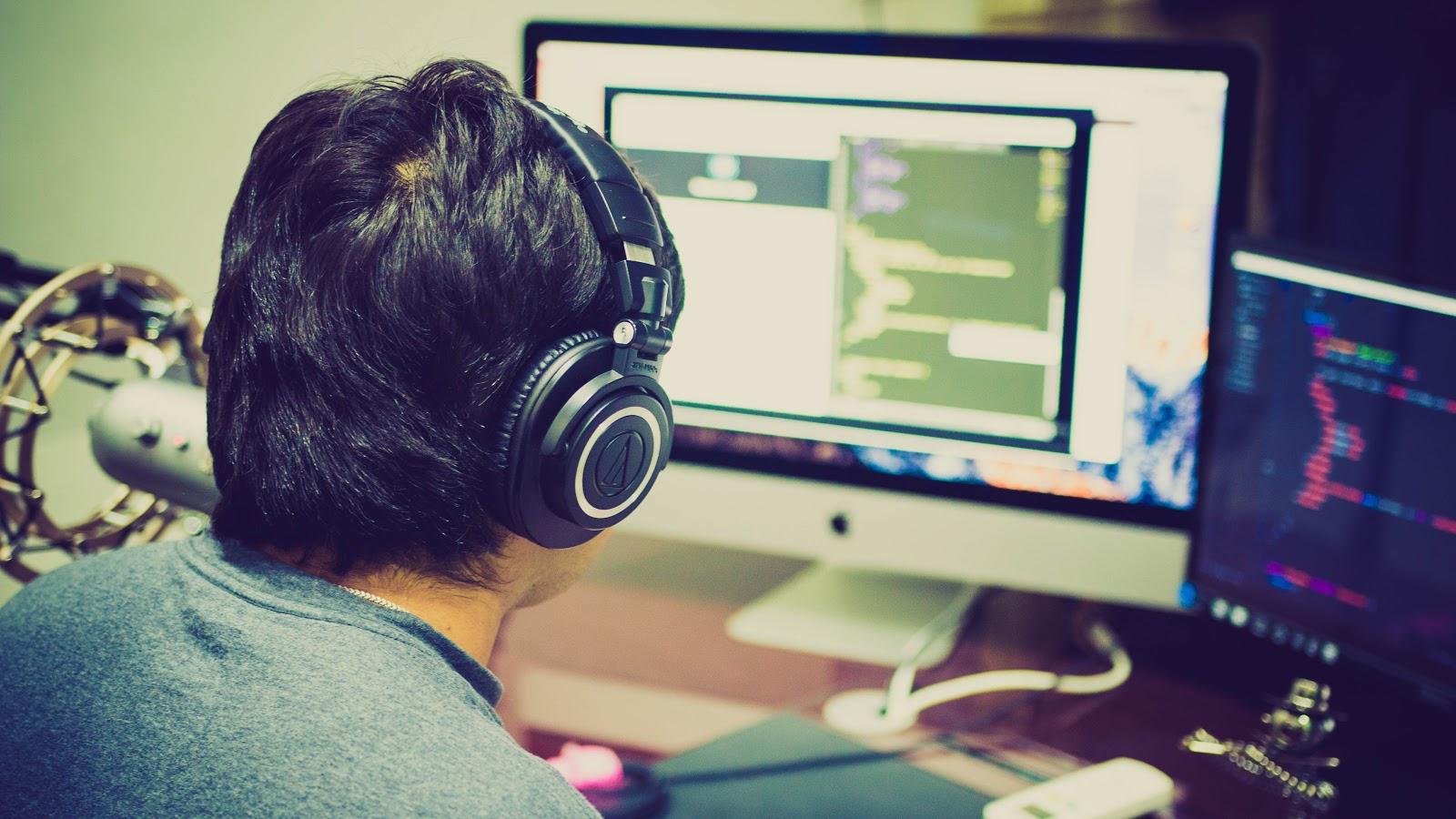 homem-concentrado-nos-computadores-a-ouvir-musica-nos-fones