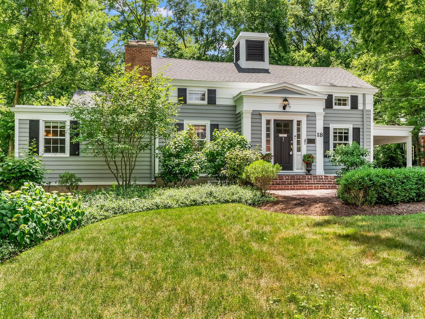 A renovated 1843 Greek Revival Home with new entry addition featuring gray siding with white trim, a portico entry with black door and red brick steps.