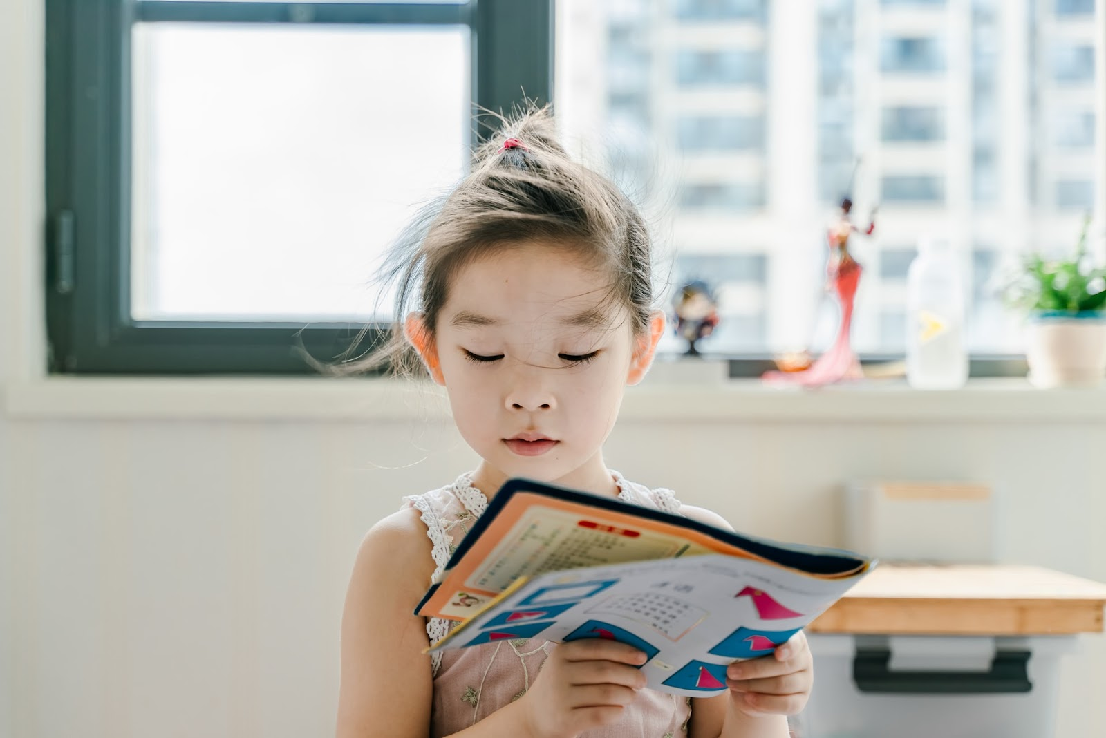 A young girl reads a book about paper oragami.