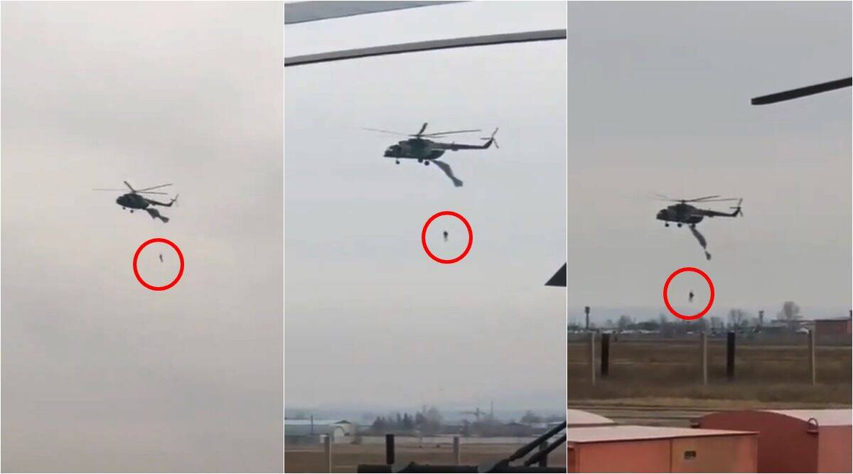 russian soldier hanging from helicopter, parachutist dangling from helicopter, russia parachute caught on helicopter, viral videos, odd news, indian express