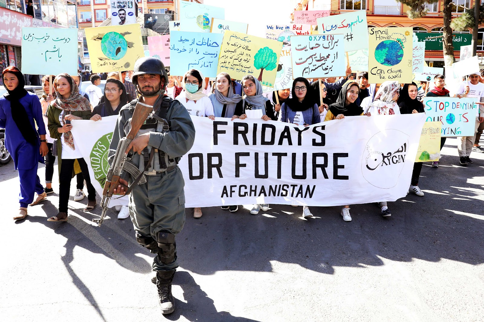 Young women leading a Fridays for Future march in Afghanistan, with a soldier at the front of the group.