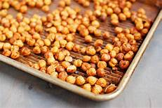 Picture of roasted chickpeas on a baking sheet. Chickpeas are a nutritious and delicious snack packed full of vitamins and minerals.