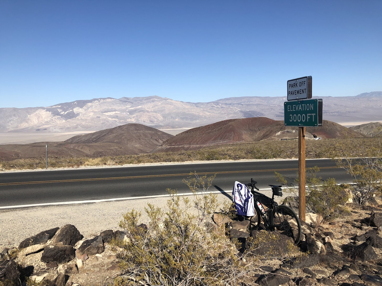 Climbing by bike Panamint Grade - bike with pjamm jacket leaning against 3000 foot sign