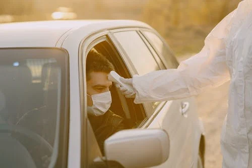 A staff member checking the temperature of the customer in his own car before he enters the salon to make sure all the social distancing guidelines are followed
