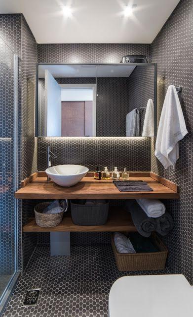 Banheiro com revestimento hexagonal em tamanho pequeno nas paredes e piso, bancadas da pia e prateleira de madeira, cuba branca e cestos de palha com utensílios.