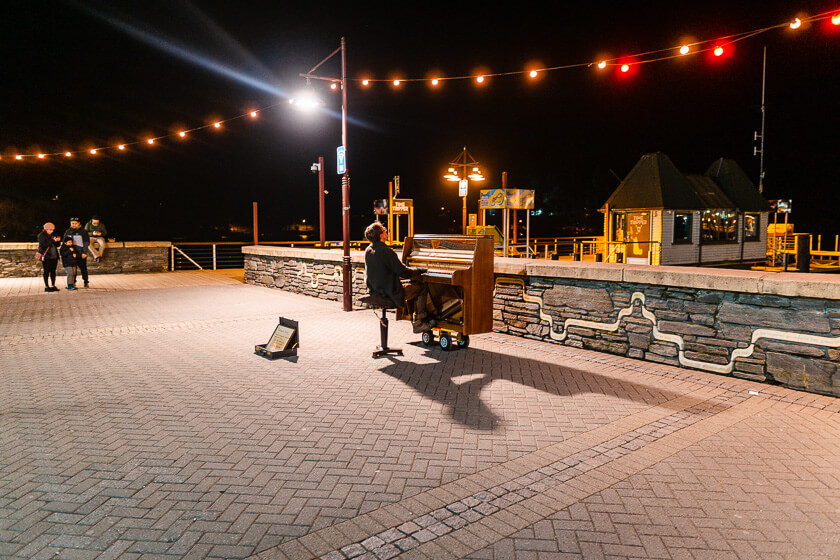 Queenstown busker by the lake at night.
