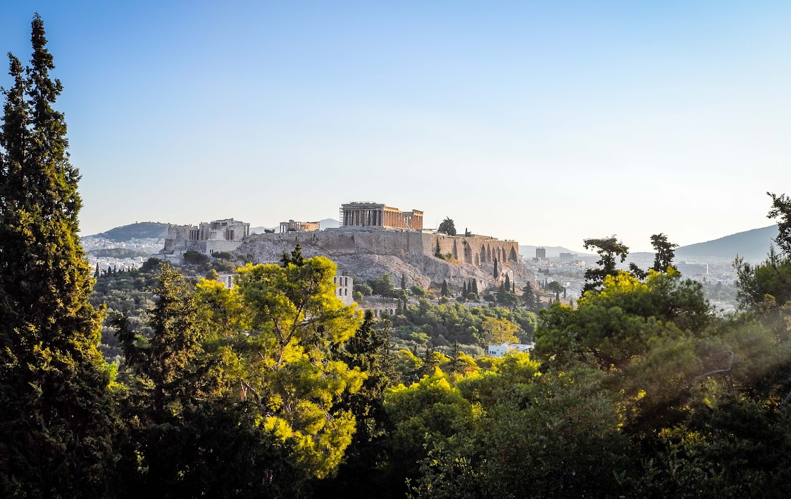 acropolis athens monumental ancient parthenon, seen behind green trees and athens skyline on a clear day.