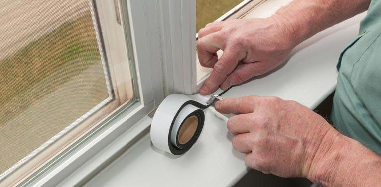 hombre-colocando-burletes-ventana-aislar-frio