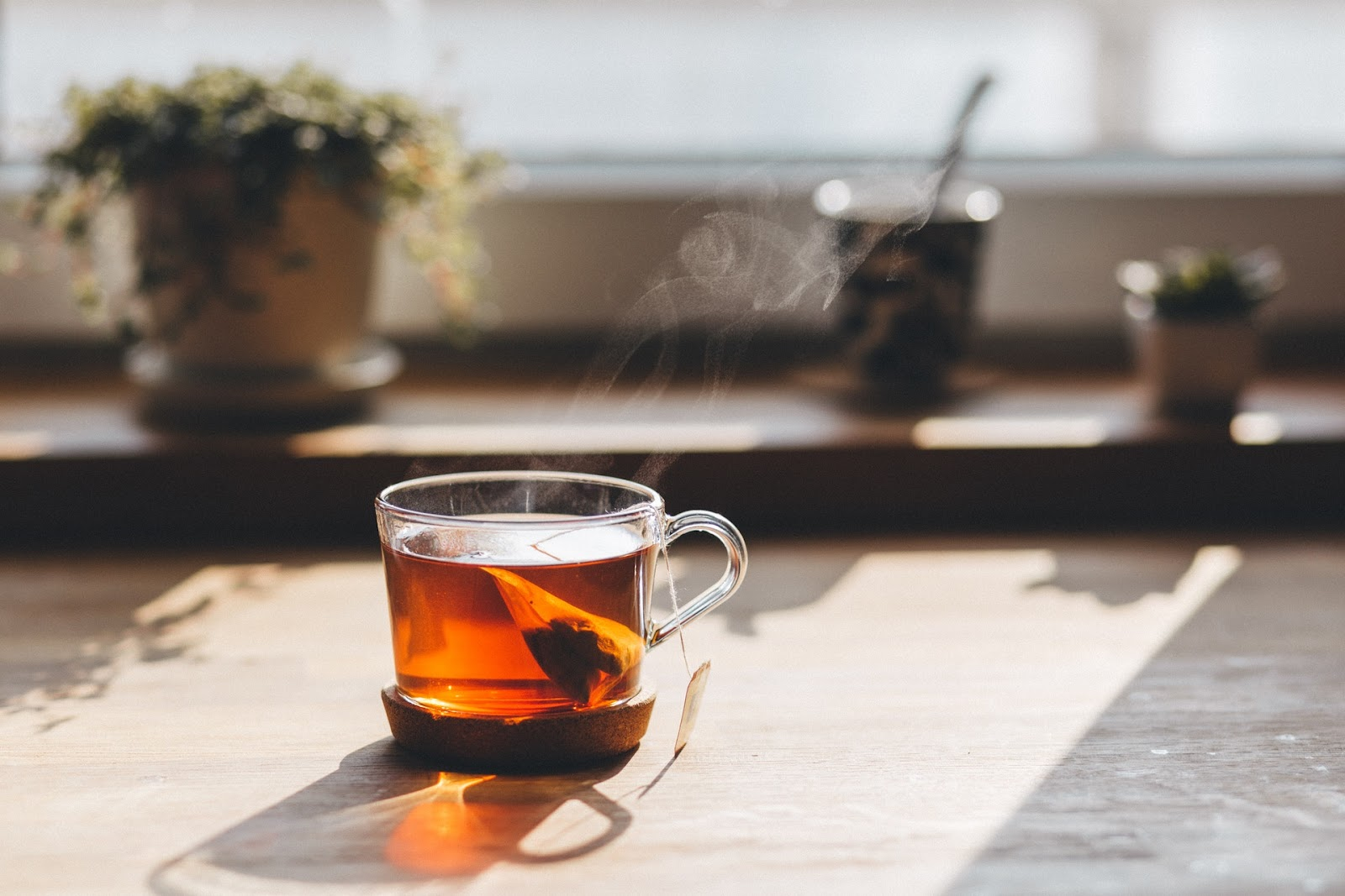 A glass cup with tea and a teabag in on a window sill.
