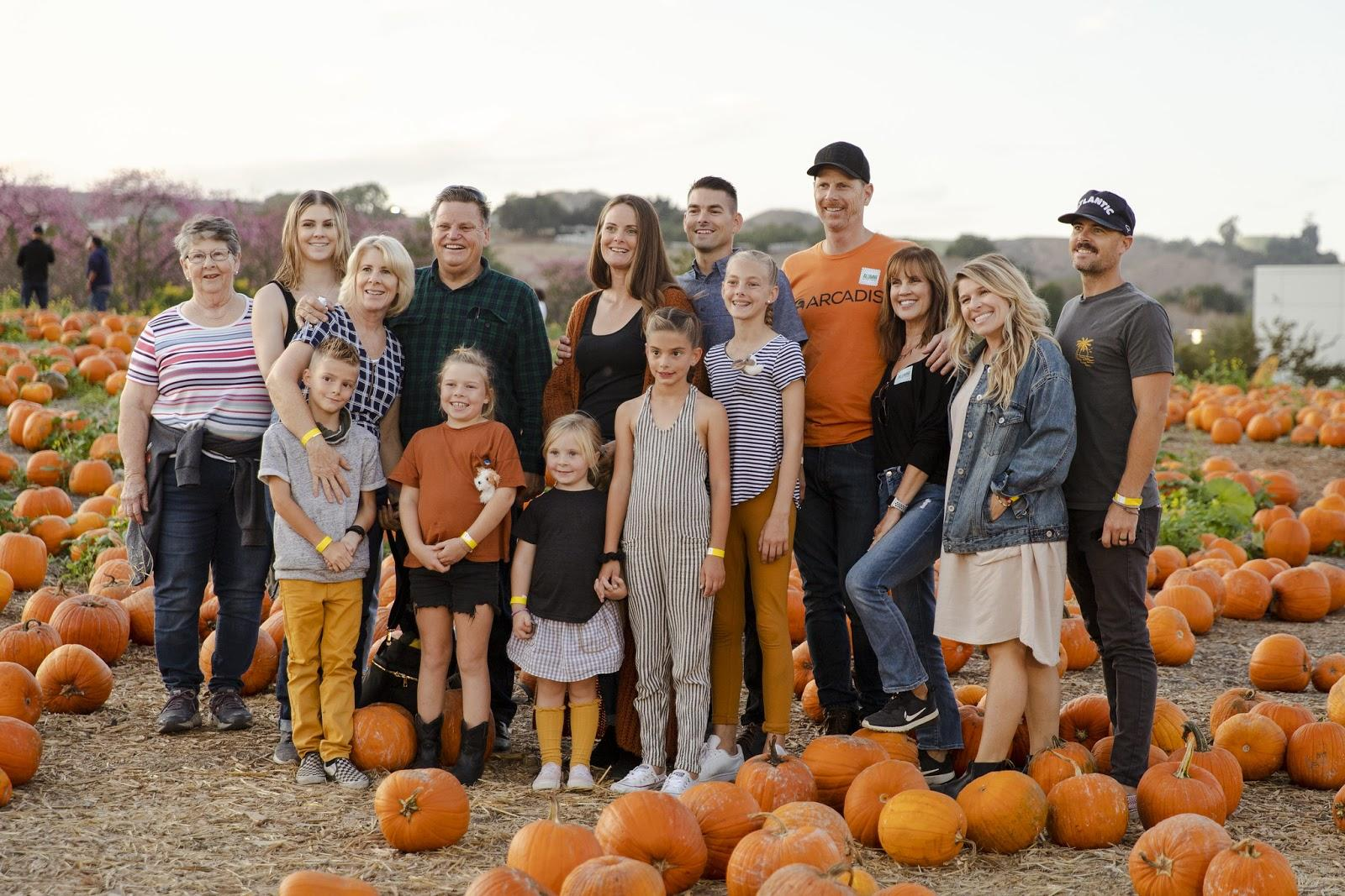 Family posing for phone in pumpkin patch