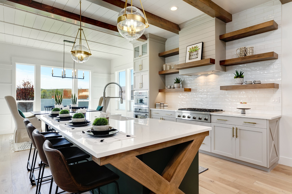 modern farmhouse kitchen with large island, wood beams, open shelving and white glossy subway tile backsplash. also featuring grey shaker cabinets, globe pendant lights and a shiplap range hood