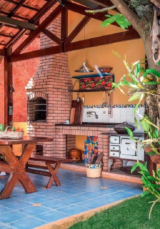 Área externa em estilo rústico com churrasqueira de tijolinhos, mesa e banco de madeira, piso de cerâmica azul, plantas e espaço com gramado.