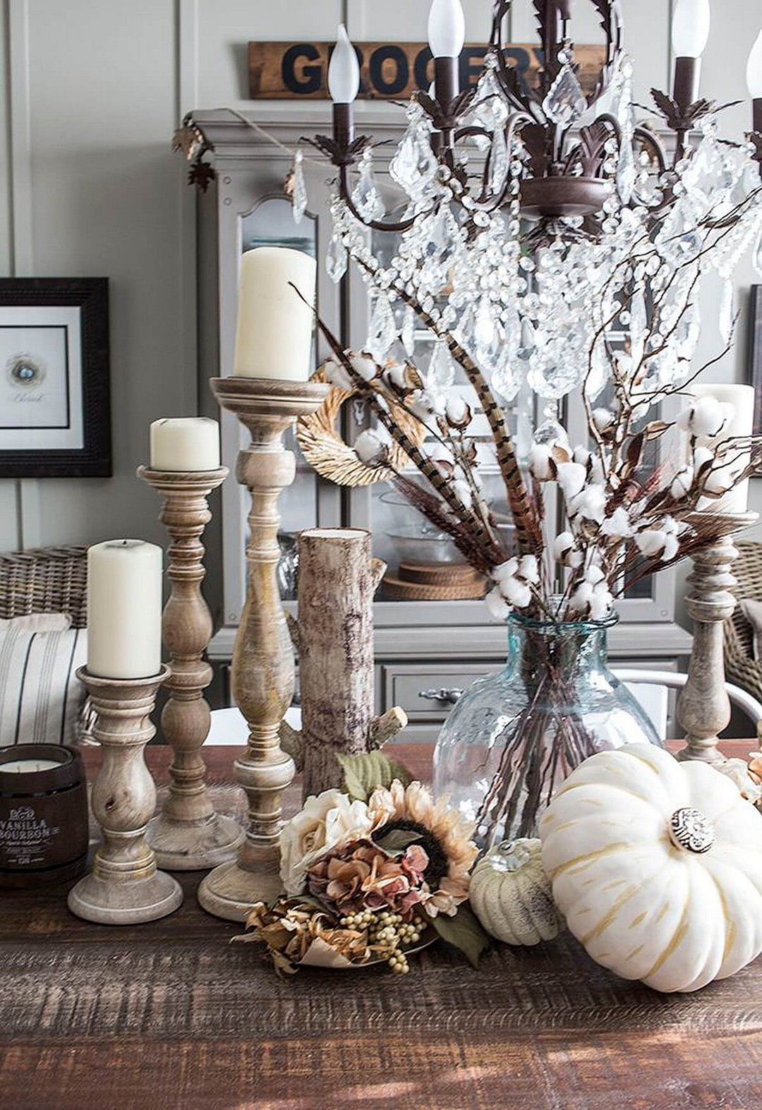 rustic fall tablescape with assorted candle holders, white pumpkins and a glass vase