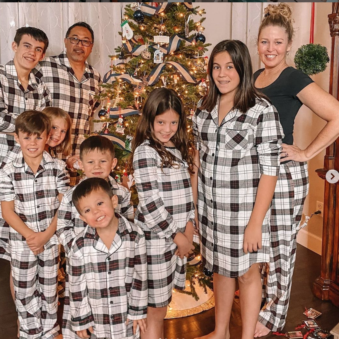 couple adopts 7 siblings and spends a winter night together in front of a decorated tree, wearing match pj's