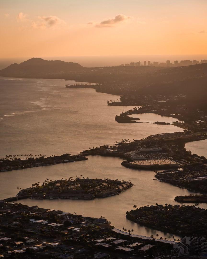 A view from above of coastline and waterways under hazy orange sky.