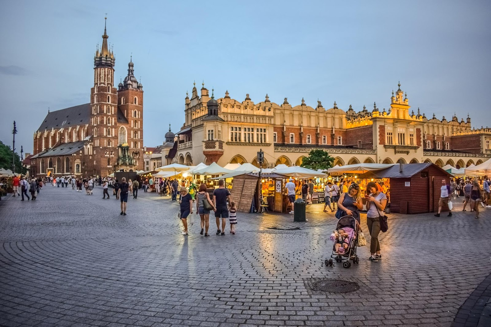 krakow main market square touristic market and tourists basilica in background during sunset