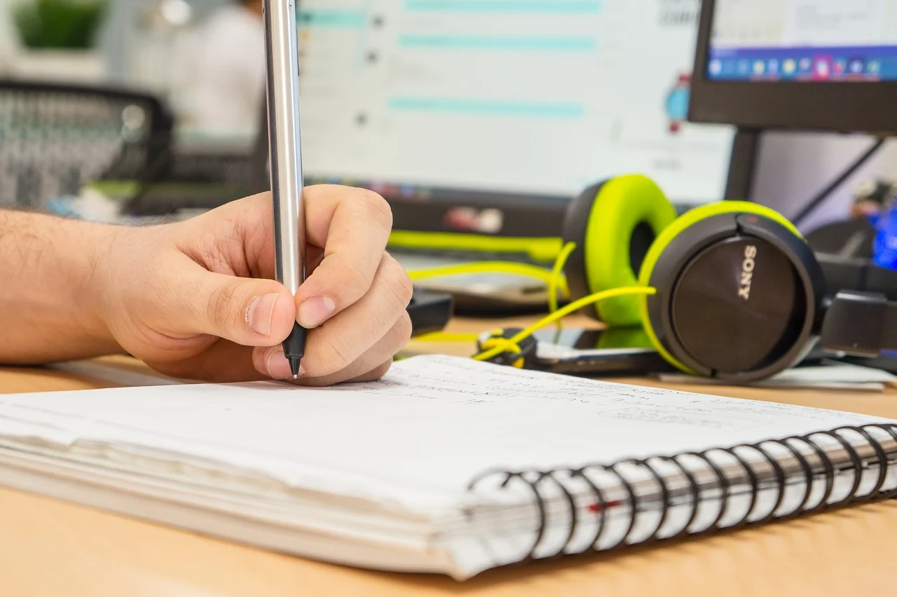 Person writing on a book with a silver pen, pair of lime green headphones