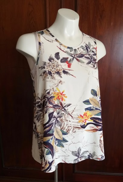 A mannequin wears a tank top with narrowed shoulders and slight scoop neck, in a beige printed rayon.