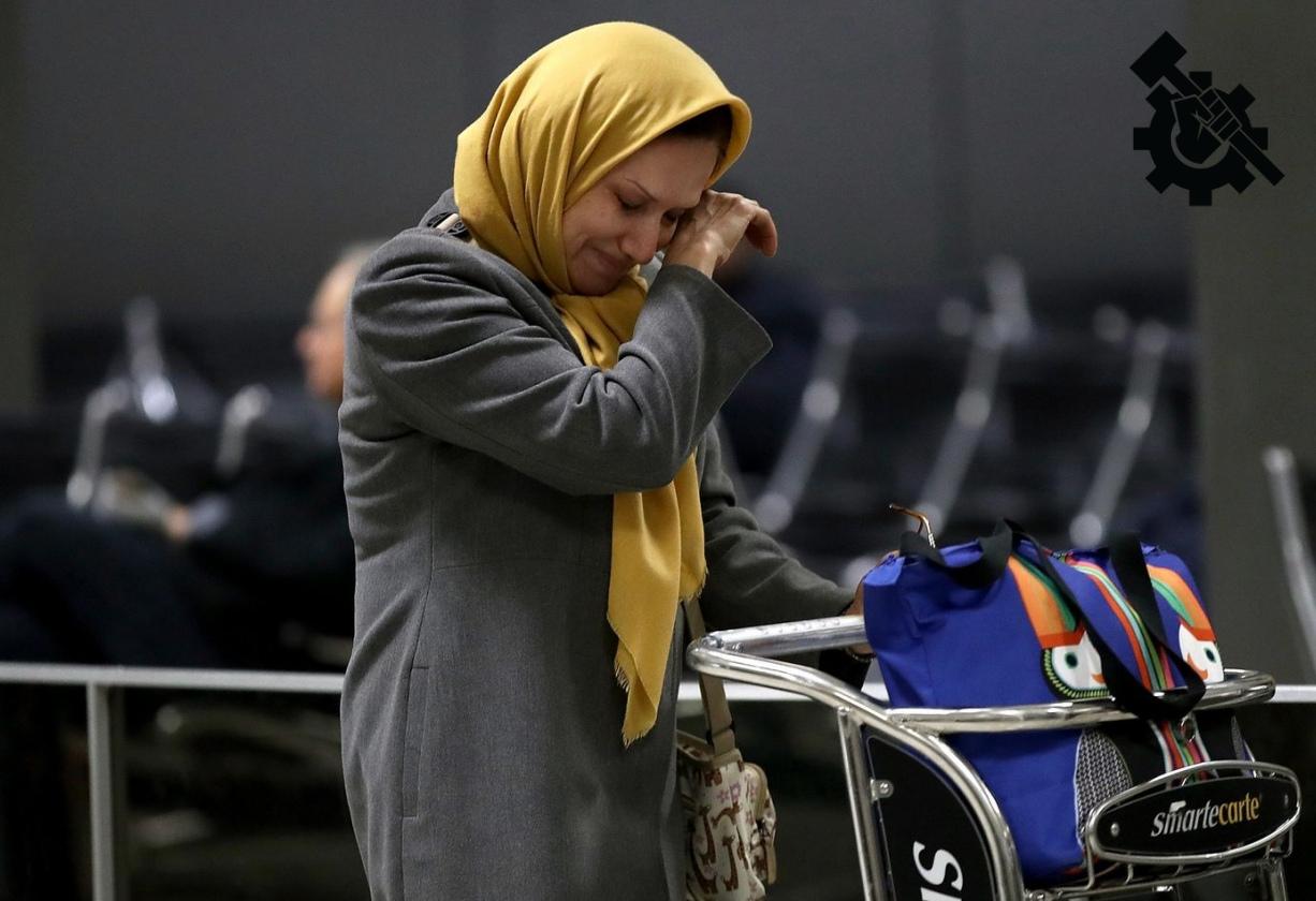 A muslim woman cries in an airport.