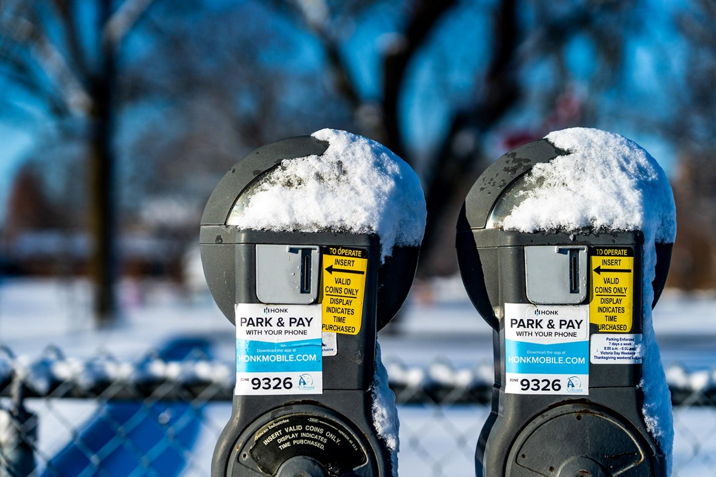 Two parking meters covered in snow after a winter storm.