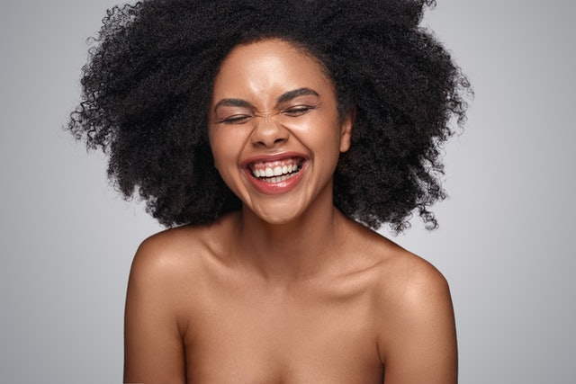 Happy young African American woman with bare shoulders laughing against gray background while representing cosmetology and skincare industry