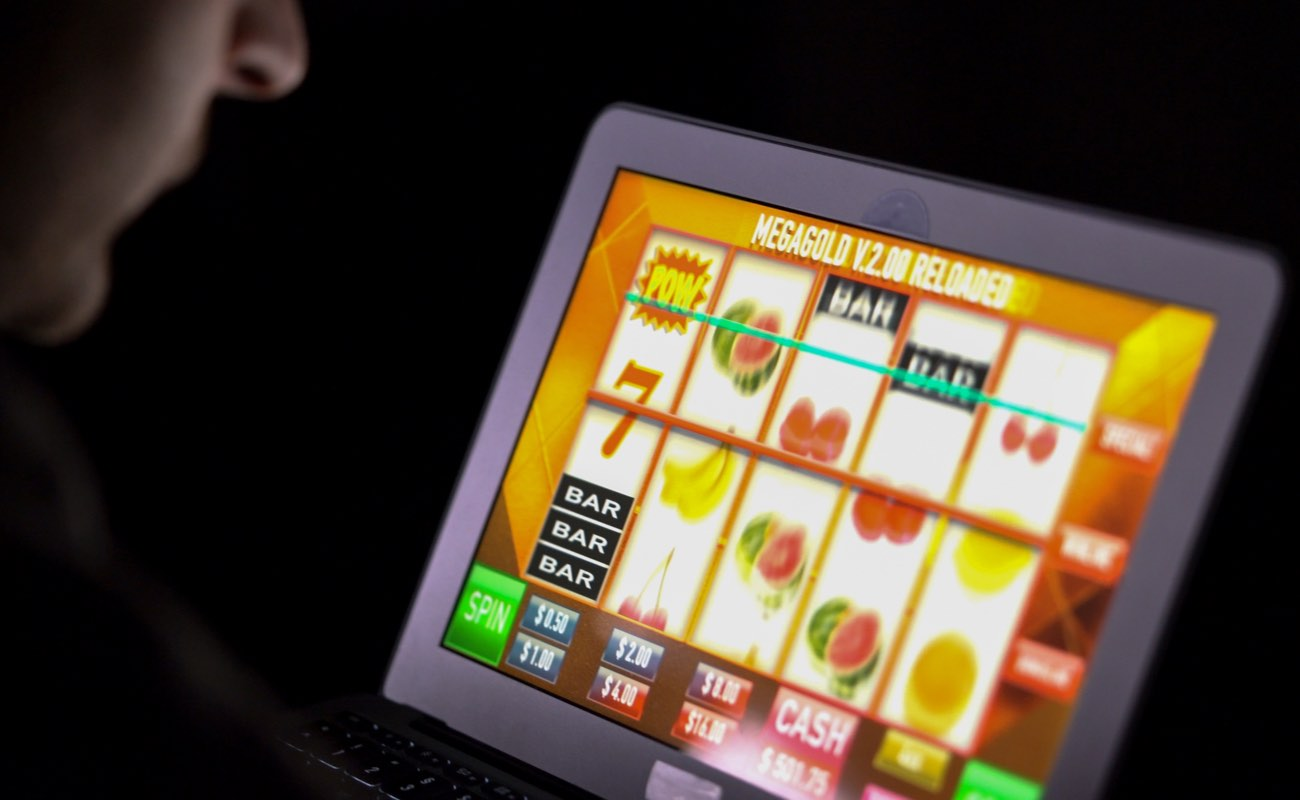 Man playing online casino slot machine on tablet