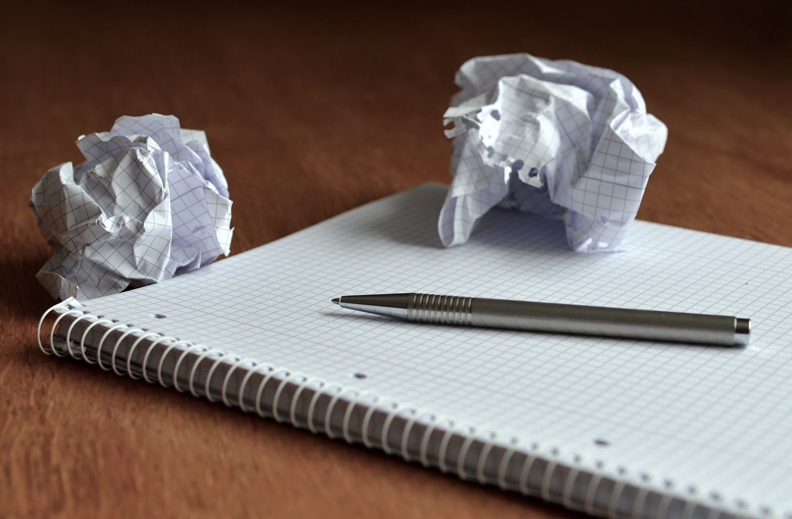 Trashed demonstrative speech ideas. Crumpled pieces of paper on a blank notebook.