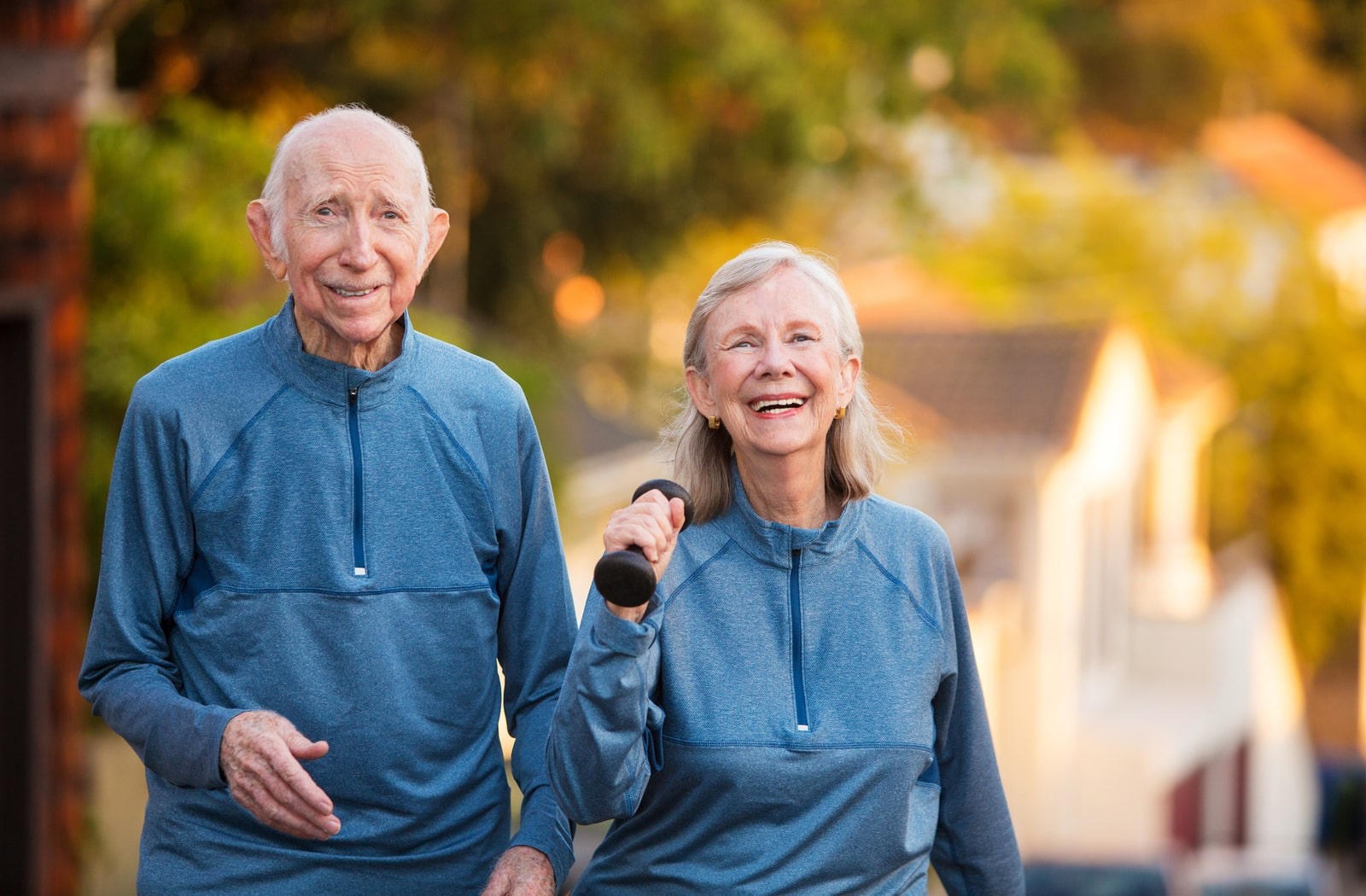 A pair of seniors in matching blue tracksuits exercising outdoors at their assisted living community