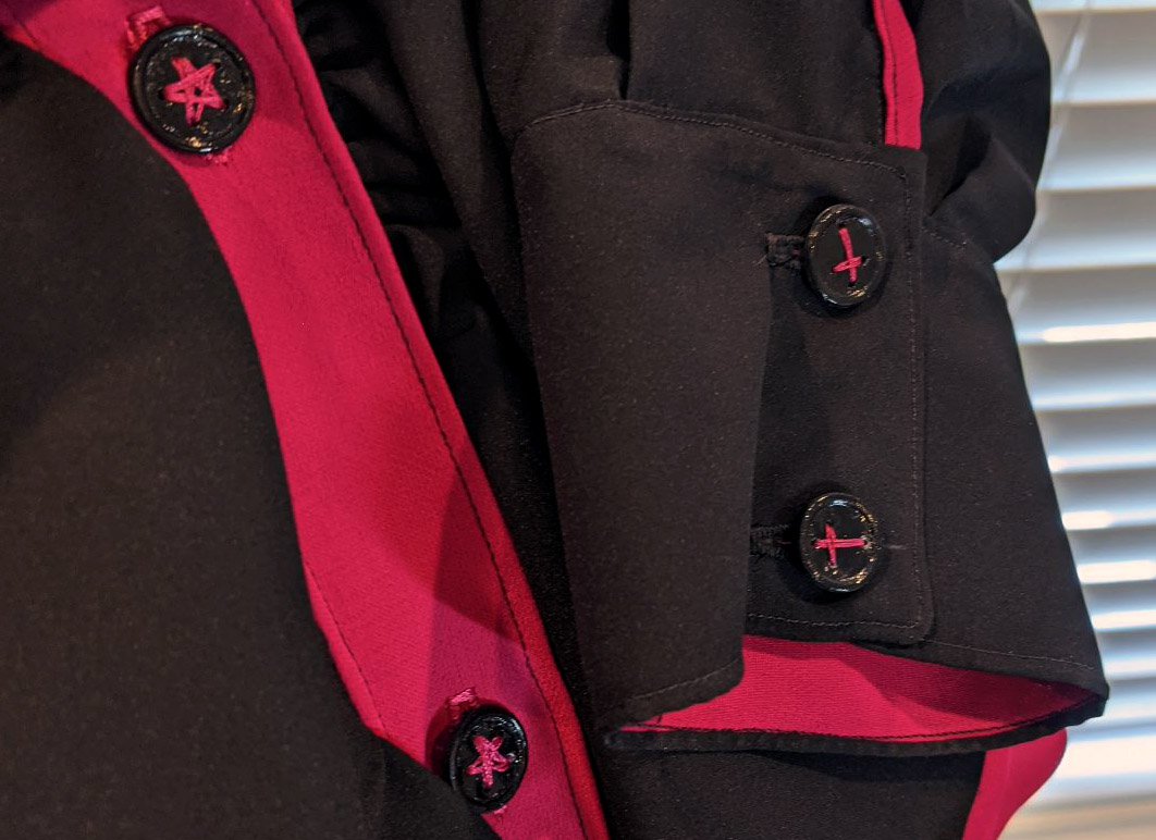 3D printed buttons (star, and cross) sewn onto a blouse