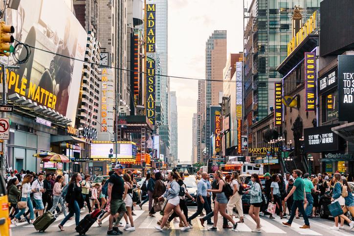 Un grupo de personas caminando en la calle de una ciudad  Descripción generada automáticamente