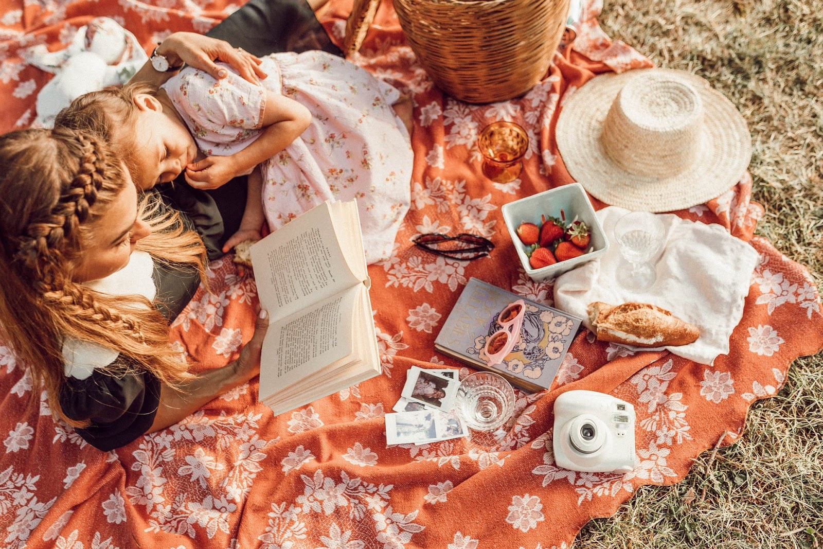 activities for people of all ages, mom and daughter reading a book when on a picnic