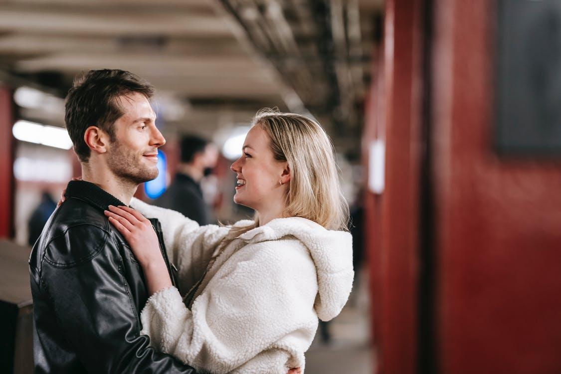 Side view of cheerful couple in trendy clothes embracing in underground corridor and looking at each other