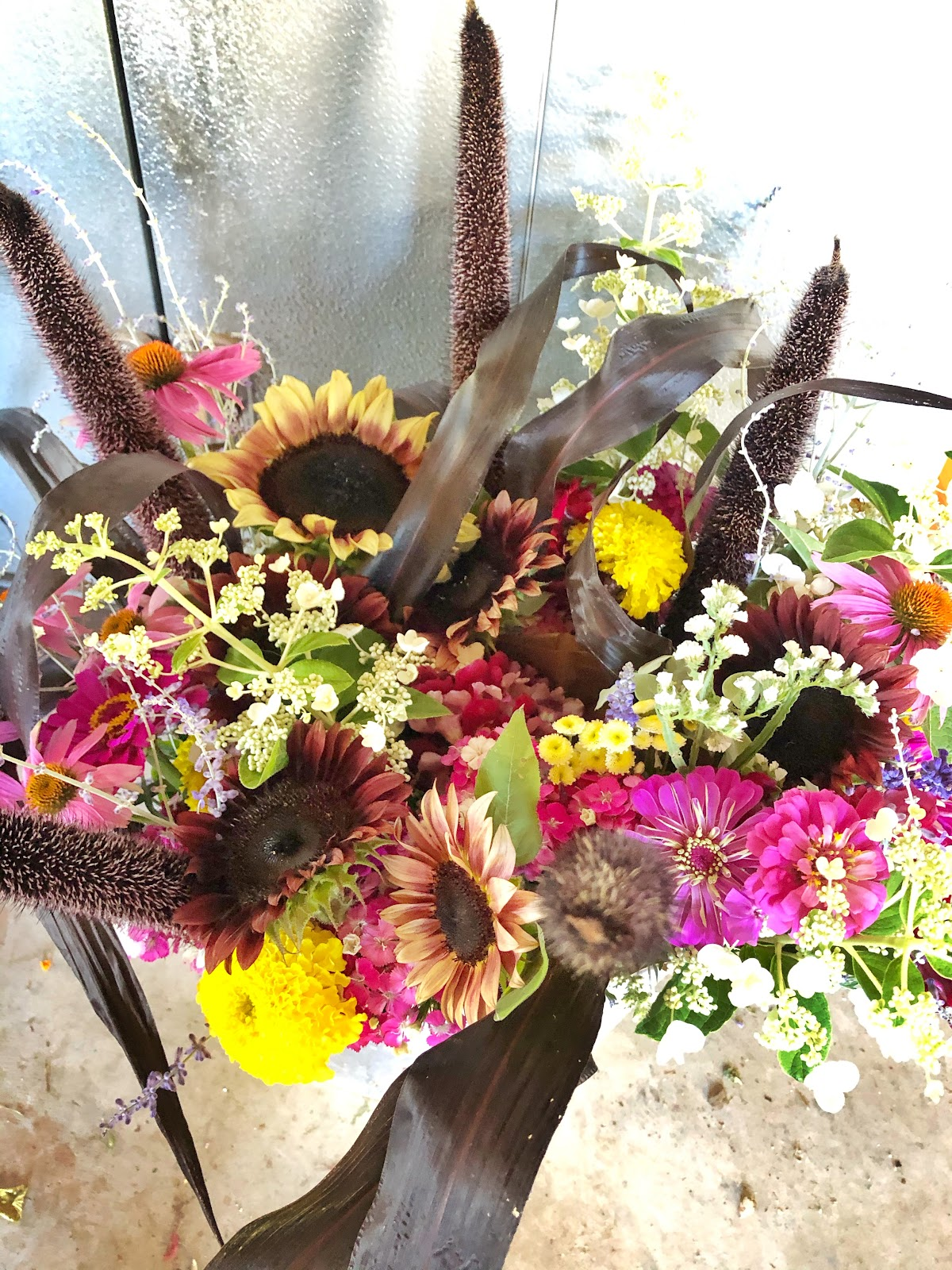 bucket with 6 bouquets featuring red, purple and yellow flowers including sunflowers, hydrangea and zinnias